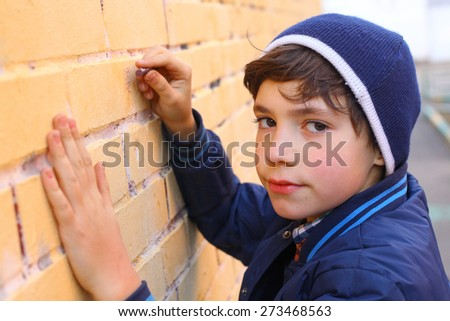 preteen handsome boy try himself as a graffiti artist on the yellow brick wall - stock photo