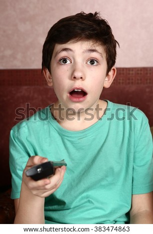 preteen handsome boy watch horror movie with remote control - stock photo