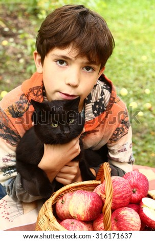 preteen handsome boy with black cat and red apples close up portrait - stock photo
