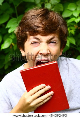preteen handsome boy with book bored yawning close up portrait - stock photo