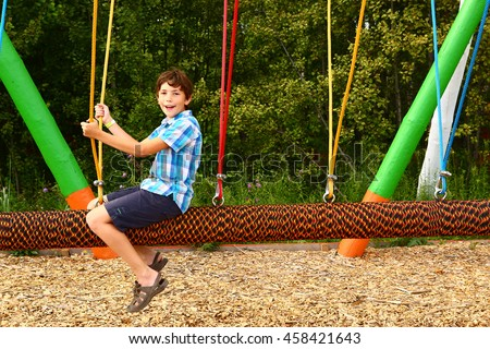 preteen happy boy in outdoor amusement park attraction log swing  close up laughing smiling portrait - stock photo