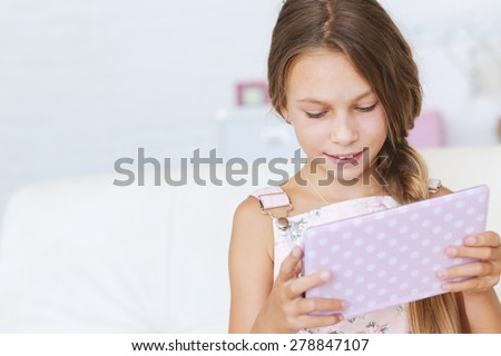 Preteen school girl of 8-9 years old playing on ipad tablet pc at home - stock photo