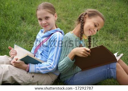 Preteen school girls reading books on green grass background outdoors - stock photo
