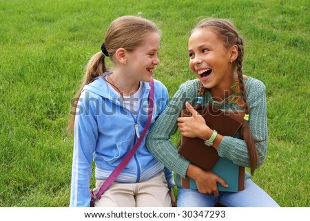 Preteen school girls with books on green grass background outdoors - stock photo