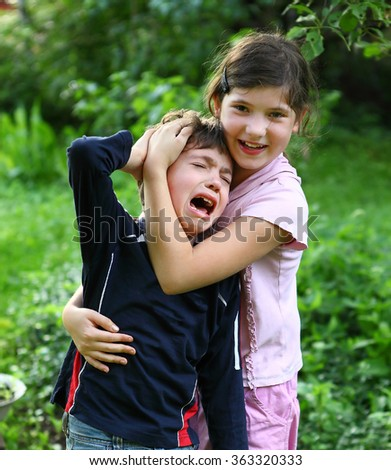 preteen sister girl  comforting and hugging crying brother boy who got blow in head and cry - stock photo