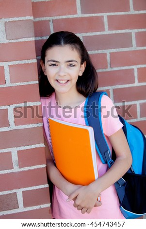Preteenager girl next to a red brick wall with the backpack and books - stock photo