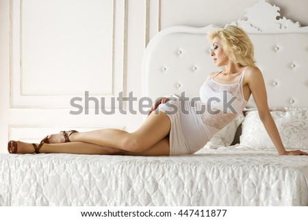 Pretty adult blonde woman wearing white dress laying on bed at a hotel room. - stock photo