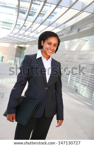 Pretty African American business woman smile with a folder - stock photo