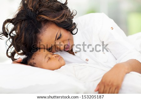 pretty african american mother looking at her sleeping baby girl - stock photo