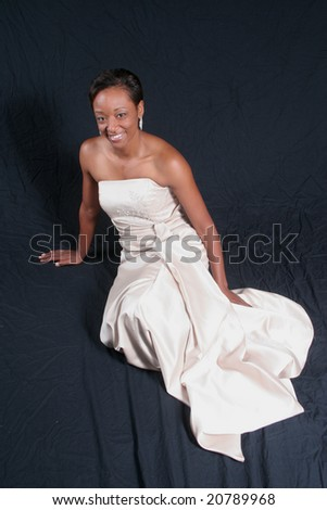 Pretty african american woman, sitting in a formal, white dress - stock photo