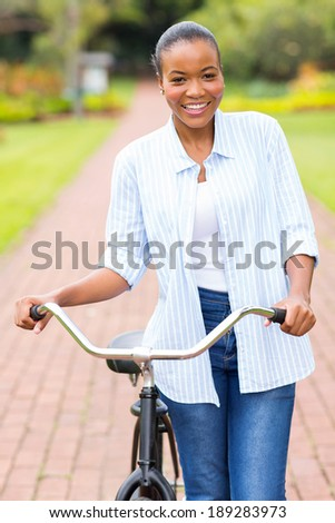 pretty african american woman walking with a bike in park - stock photo