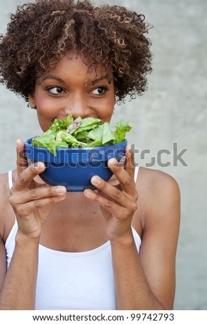 pretty African American woman with a healthy salad - stock photo
