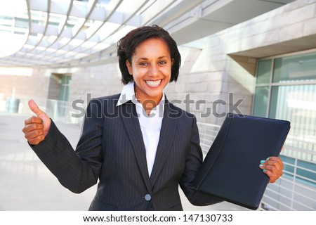 pretty african businesswoman thumbs up with a folder - stock photo
