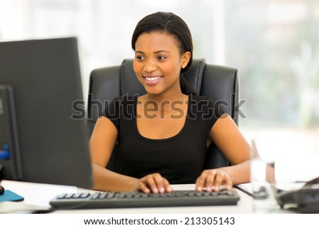 pretty african businesswoman using computer - stock photo
