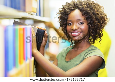pretty african college girl looking for book in library - stock photo