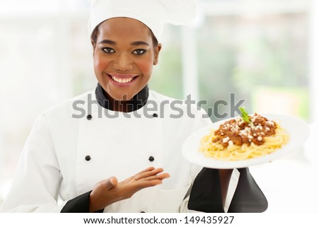 pretty african female chef holding spaghetti dish - stock photo