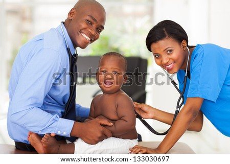 pretty african female nurse examining little boy with male doctor - stock photo