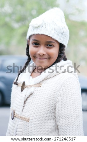 Pretty african girl with winter clothes in the park - stock photo