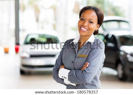 pretty african vehicle saleswoman with arms crossed in showroom - stock photo