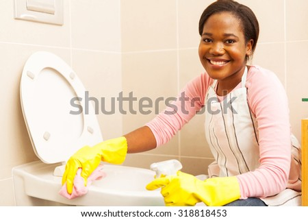 pretty african woman cleaning toilet - stock photo