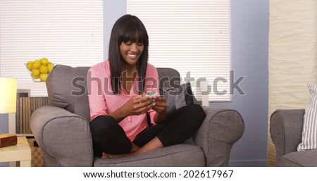 Pretty african woman using smartphone at home - stock photo