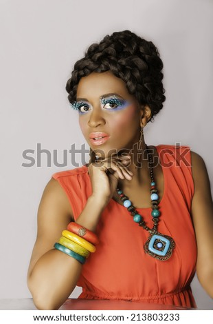 Pretty African woman with colorful accessories and makeup, an elaborate braided hairstyle and an orange dress, posing against a white background - stock photo