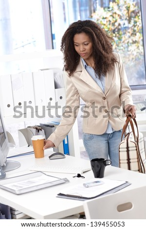 Pretty afro-american businesswoman arriving at office, having coffee. - stock photo
