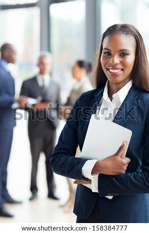 pretty afro american businesswoman holding laptop in office - stock photo
