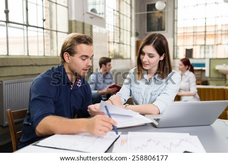 Pretty and Handsome White College Friends Busy Discussing Reports at the Worktable with Laptop Computer. - stock photo
