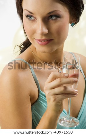 pretty and young brunette with a glass of champagne looking on one side - stock photo