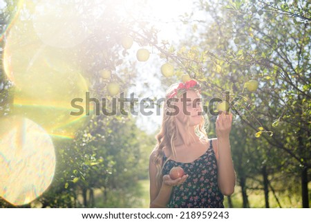 pretty apple fairy: young woman cute blond girl smiling among red apples with wreath of flowers & sun light flares of rays on summer outdoor copy space background - stock photo