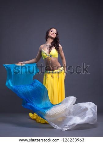 Pretty arabic dancer in yellow costume - stock photo