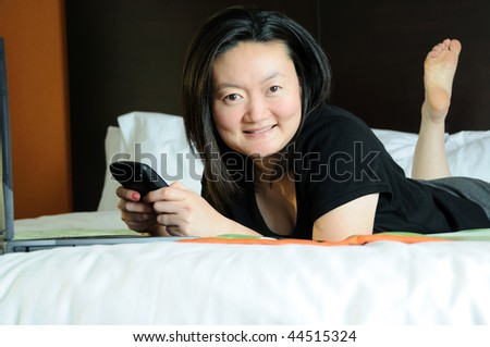 Pretty Asian business woman checks PDA or smartphone in hotel room - smiling at camera - stock photo