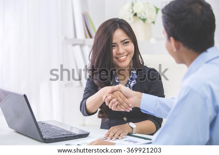 Pretty asian business woman shaking hands with businessman in her office during meeting - stock photo