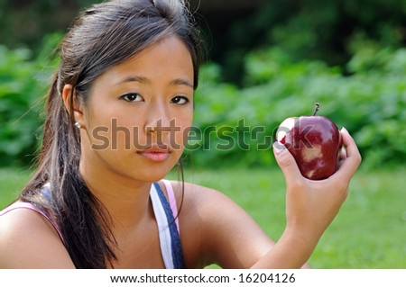 Pretty Asian woman holding apple with bite mark - stock photo