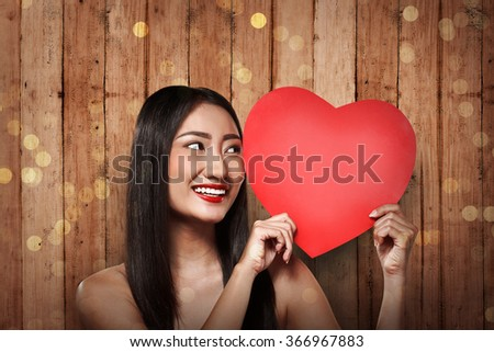 Pretty asian woman holding red paper with heart shape. Valentine day concept - stock photo