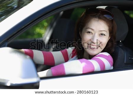 Pretty Asian women in a white car happy driving - stock photo