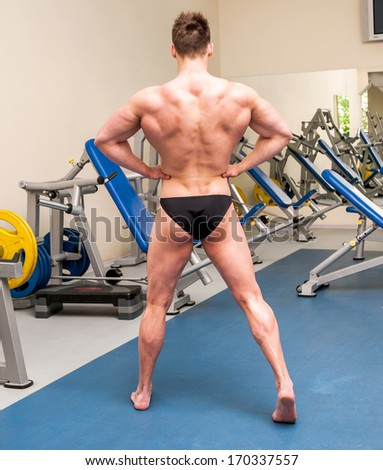 pretty athletically built sportsman posing in the gym - stock photo