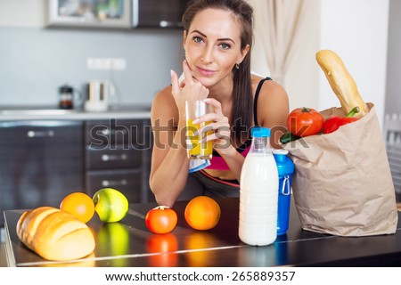 Pretty attractive athletic active sportive lady woman standing in kitchen and healthy food fresh fruits milk bread around holding glass with juice. - stock photo