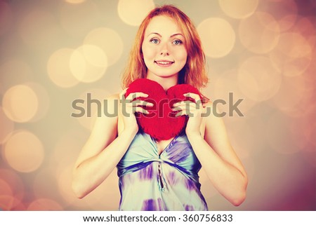 Pretty attractive blond woman holding a plush heart. waiting for Valentine's Day. woman's love and feelings. photo with artistic effect. vintage toning. film retro style - stock photo