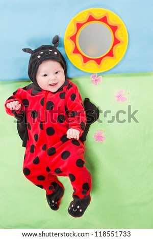 Pretty baby girl, dressed in ladybug costume on green background. The concept of childhood and holiday - stock photo