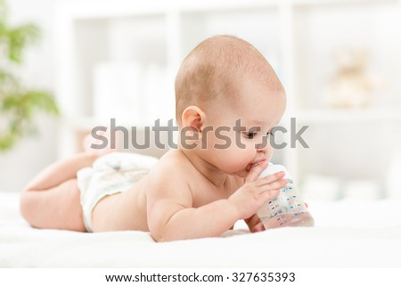 Pretty baby girl drinks water from bottle lying on bed. Child weared diaper in nursery room. - stock photo