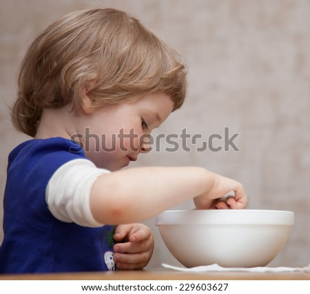 Pretty baby girl eating at home - stock photo