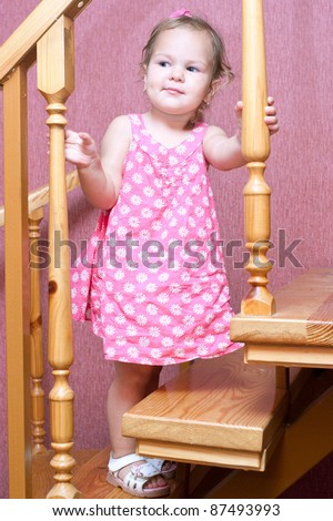 Pretty baby girl in a pink dress up the stairs in the house - stock photo