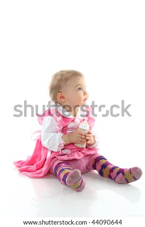 Pretty baby girl is drinking milk in a bottle isolated - stock photo