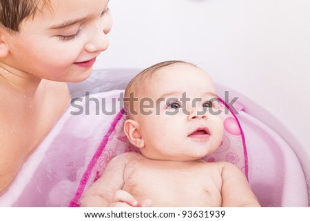 Pretty baby girl is having a bath in her bathtub with her, brother. - stock photo