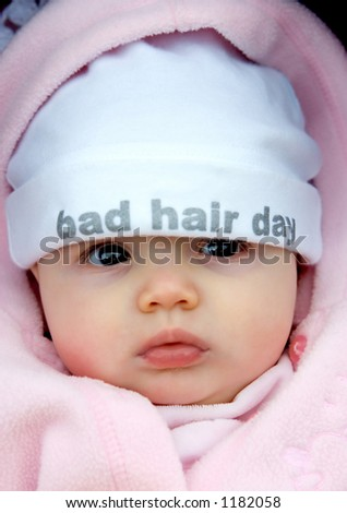 Pretty baby girl with funky hat on that says bad hair day - stock photo