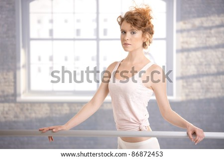 Pretty ballerina girl standing by bar in dance studio front of window.? - stock photo