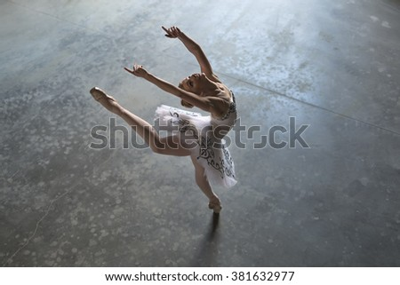 Pretty ballerina in a white tutu making a pose in a hall. She outstretches her hands and one leg up during tilting back. Daylight falls on her. Indoor. Horizontal. - stock photo