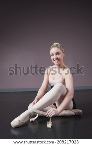 Pretty ballerina tying the ribbon on her ballet slippers in the ballet studio - stock photo